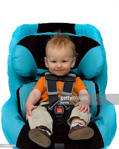 A toddler boy sitting in a blue car seat