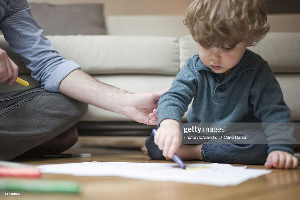 Toddler boy sitting on floor with father, drawing on paper : Stock Photo