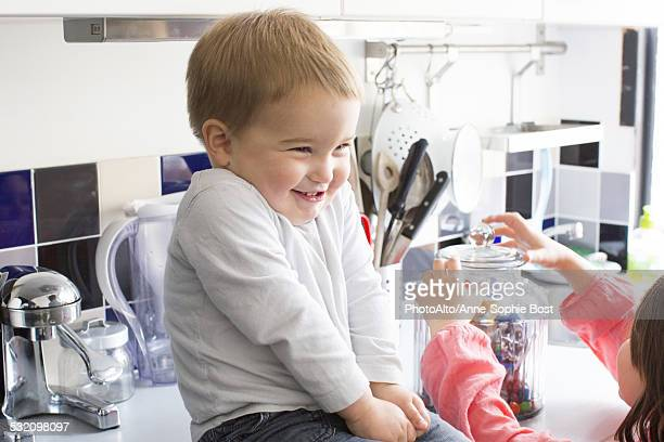 Toddler boy sitting on kitchen counter, smiling as sister reaches for candy jar