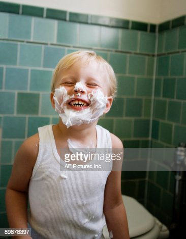 Toddler boy smiles with shaving cream on his face : Stock Photo