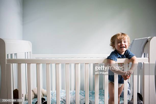 Toddler boy (21-24 months) smiling in crib, close-up