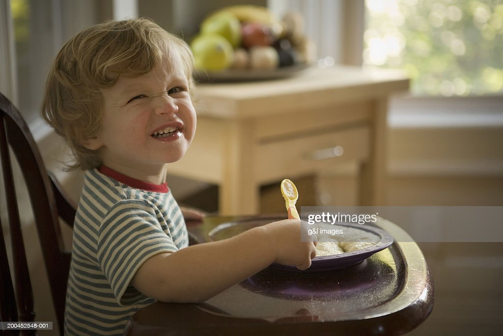 Toddler boy (21-24 months) smiling in high chair, portrait, close-up : Stock Photo
