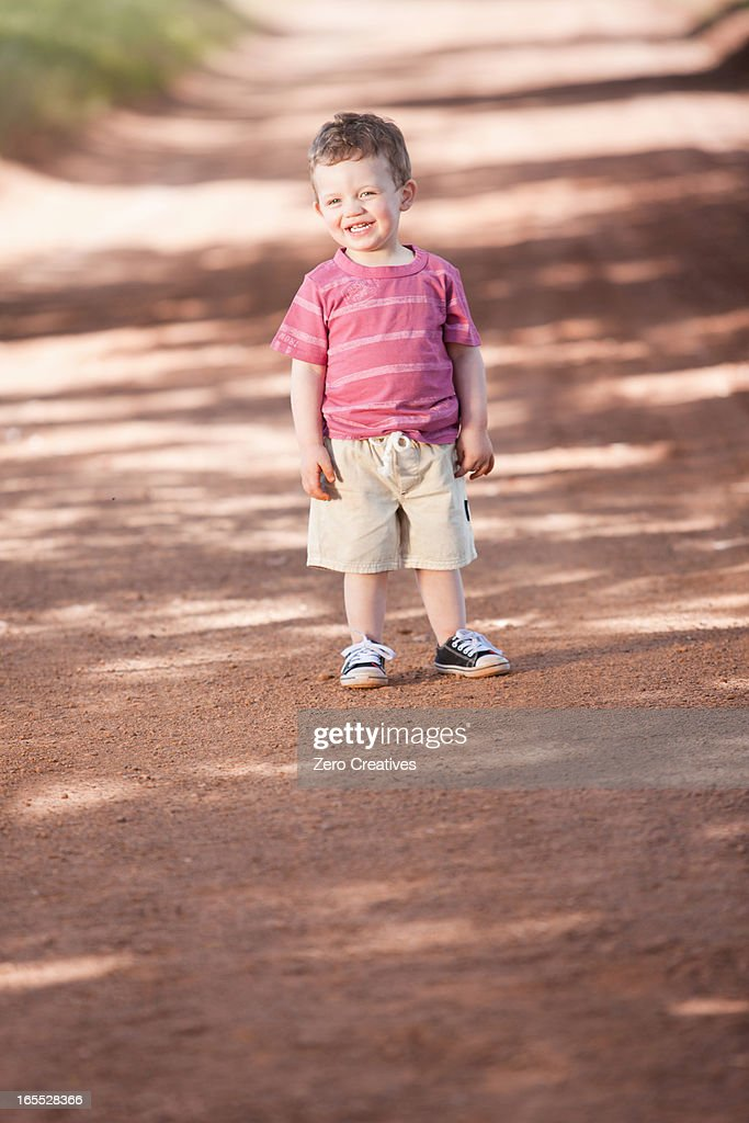 Toddler boy standing on dirt road : Stock Photo