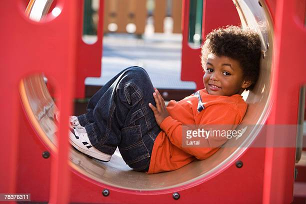 Toddler boy taking a break on playground