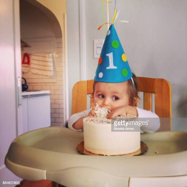 Toddler boy taking bite out of cake on first birthday