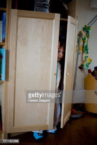 toddler boy trying playing hide & seek in bookcase : Bildbanksbilder
