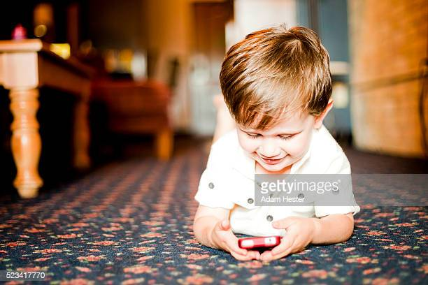 A toddler boy viewing a cell phone inside his house on the floor.