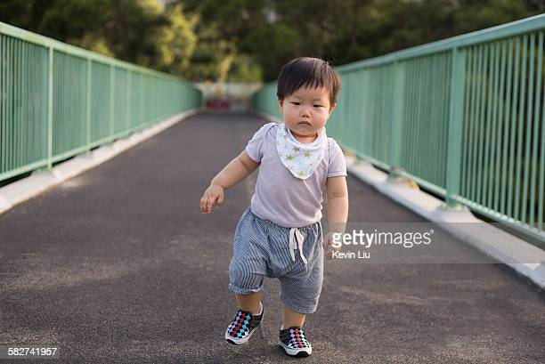 Toddler boy walking on a footbridge