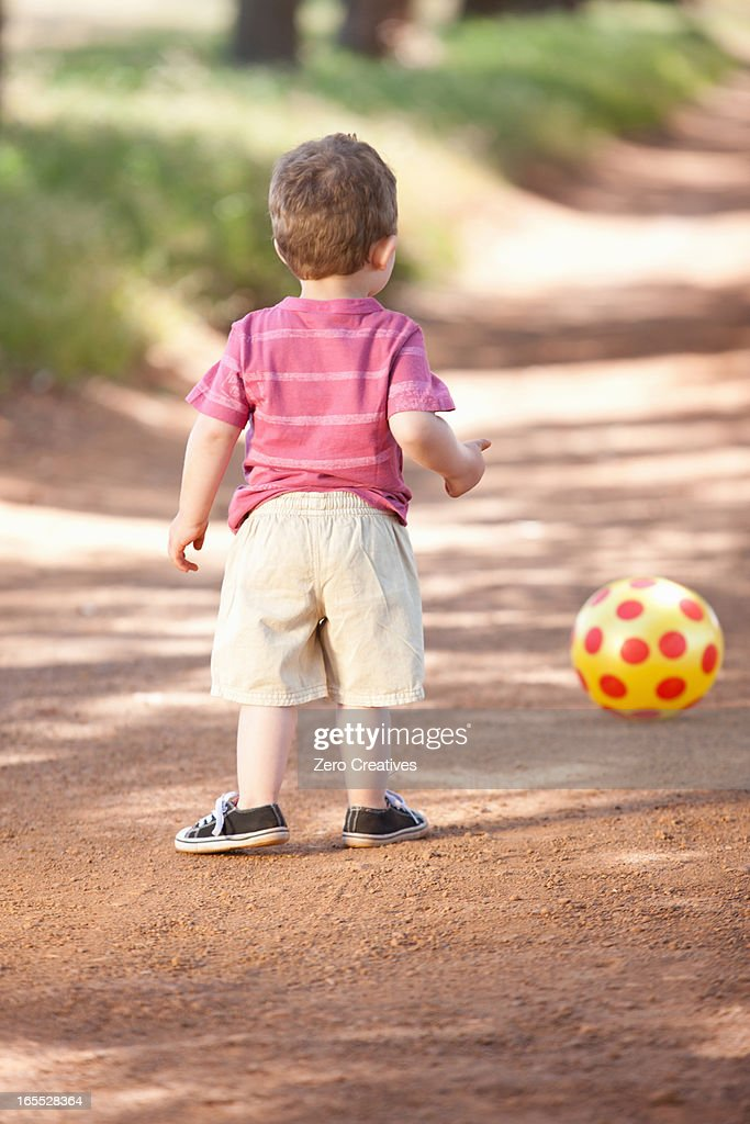 Toddler boy with ball on dirt road : Stock Photo