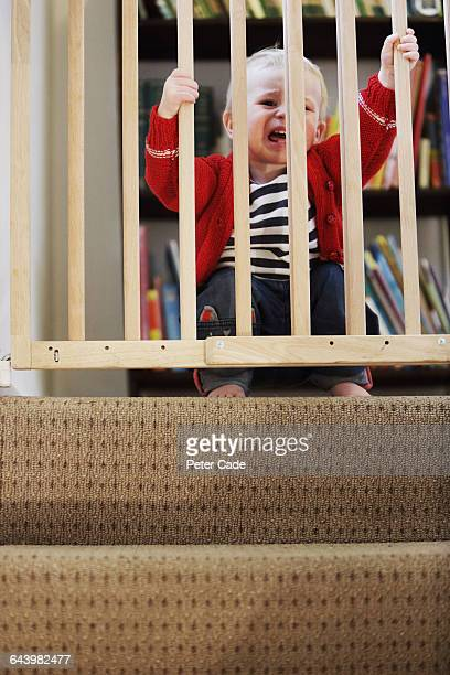 Toddler crying behind stair gate