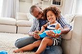 Toddler daughter sits on dadÕs knee playing ukulele at home