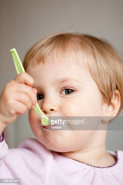 Toddler eating a yogurt, portrait