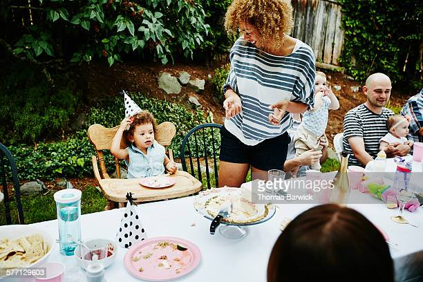 Toddler eating cake during birthday party
