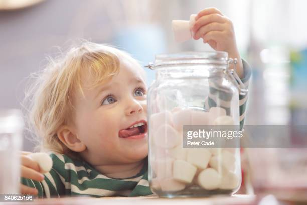 Toddler eating marshmallows from large glass jar