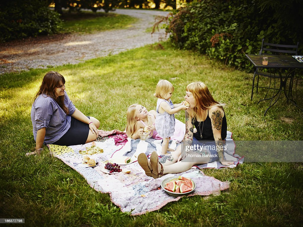 Toddler feeding mom sandwich outdoors : Stock Photo