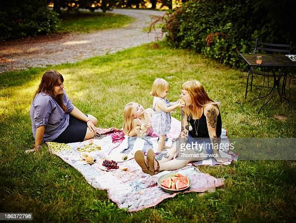 Toddler feeding mom sandwich outdoors