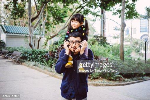 Toddler gilt sitting on dad's shoulders in park