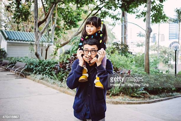 Toddler gilt sitting on dad's shoulders in park