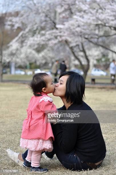A toddler girl and her mother kissing with love