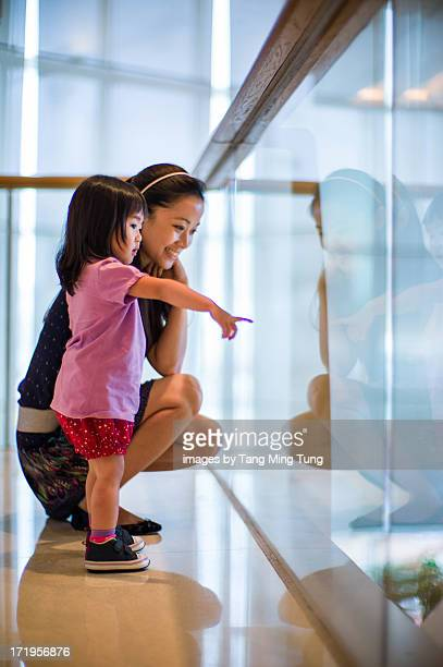 Toddler girl and young mom in shopping mall