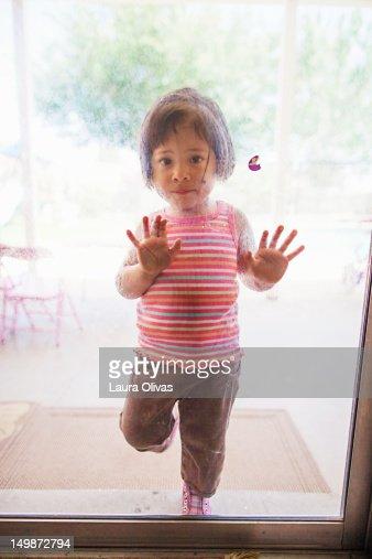 Toddler girl at sliding glass door : Stock Photo