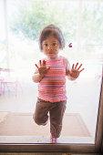 Toddler girl at sliding glass door