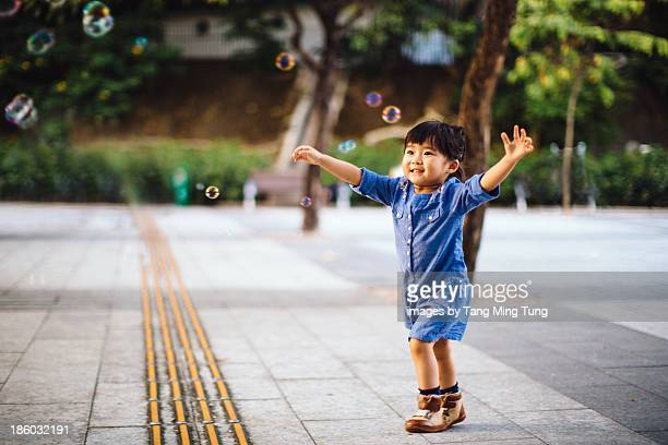 Toddler girl catching bubbles joyfully in park