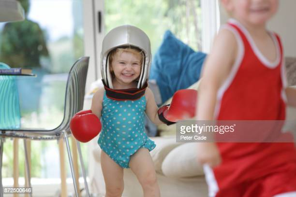 Toddler girl chasing brother in house in swimming costume and boxing clothes