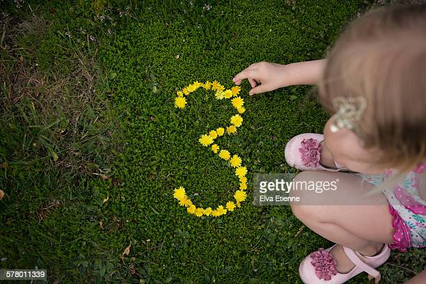 Toddler girl creating number three with flowers