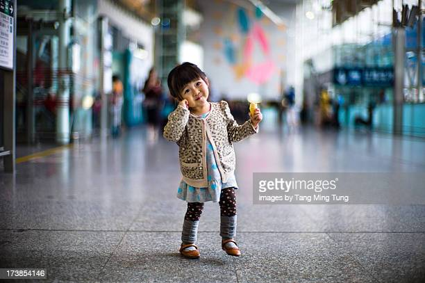 Toddler girl dancing joyfully in train station