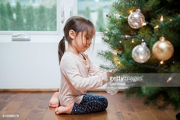 Toddler girl decorating Christmas tree