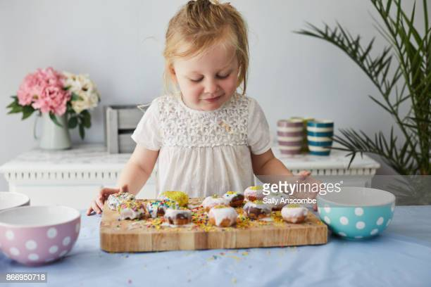 Toddler girl decorating doughnut with sprinkles