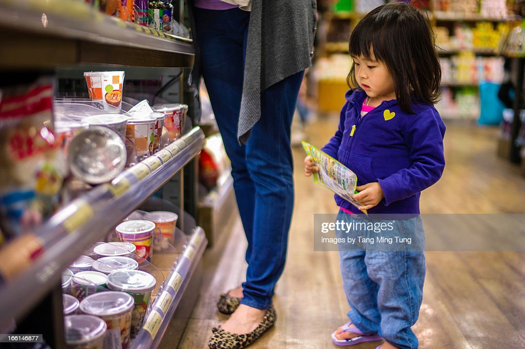 Toddler girl doing grocery shopping with mom : Stock Photo
