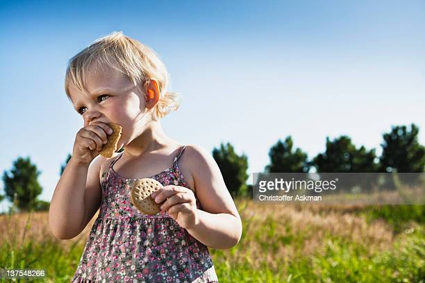 Toddler girl eating crackers outdoors