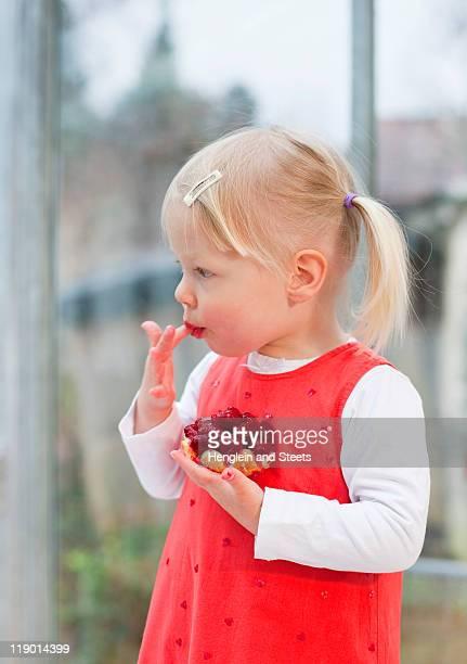 幼児の女の子のフルーツケーキを食べる