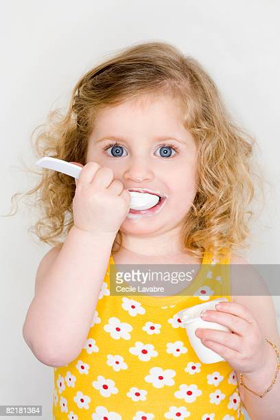 Toddler girl eating yogurt