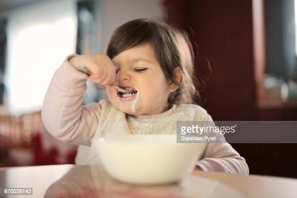 Toddler girl enjoying a bowl of breakfast cereal