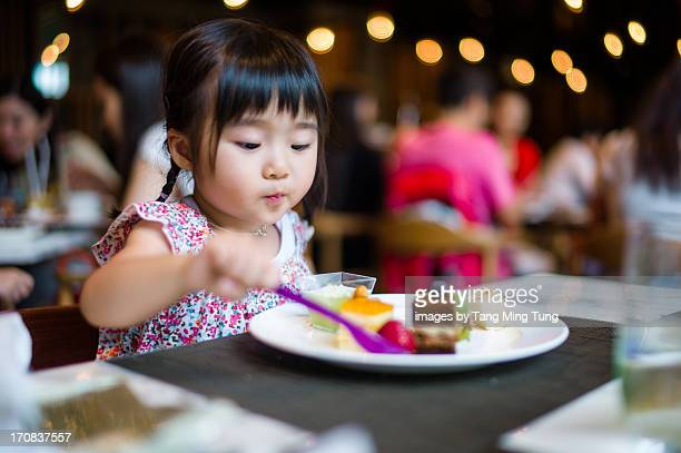 Toddler girl enjoying her dessert buffet