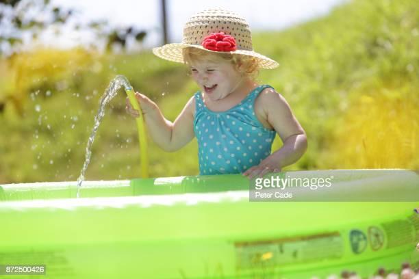 Toddler girl filling up paddling pool in garden