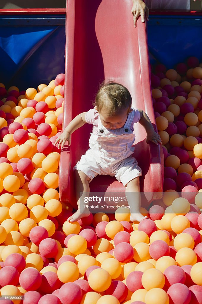 Toddler girl going down slide into ball pit on playground : Stock Photo
