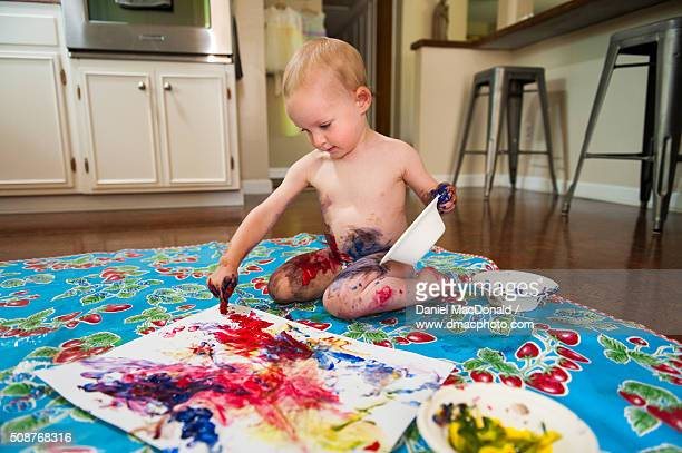 Toddler girl happily finger painting and making a mess