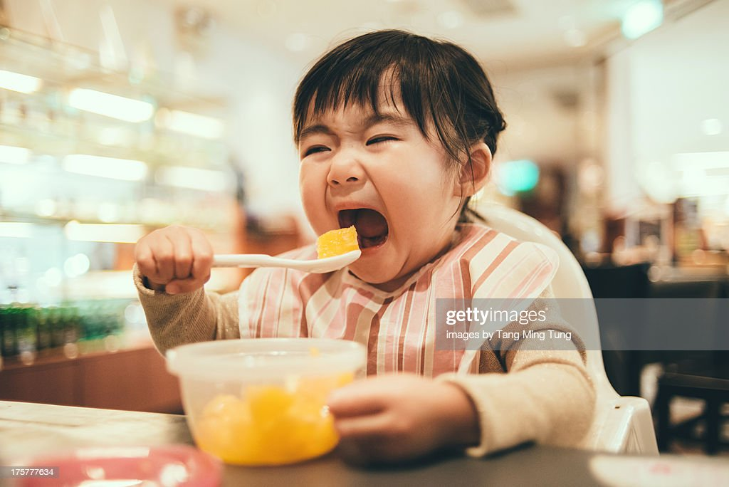 Toddler girl having chopped orange in a restaurant with her mouth wide opened.