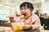 Toddler girl having chopped orange in a restaurant