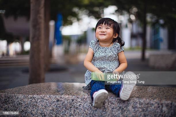 Toddler girl having fruit on the bench