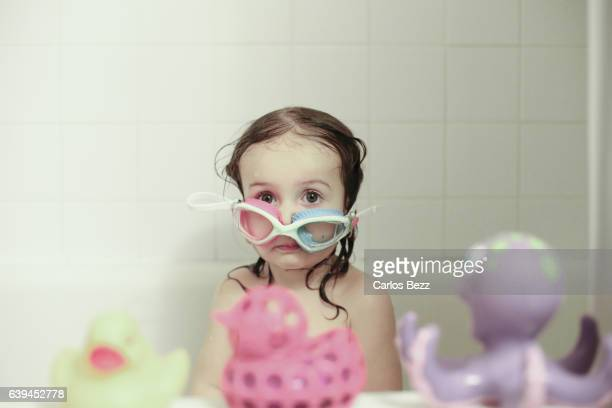 toddler girl having fun in bathtub