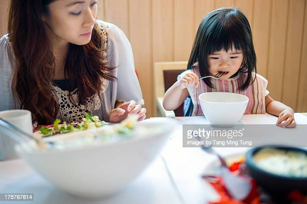 Toddler girl having lunch with mom in restaurant
