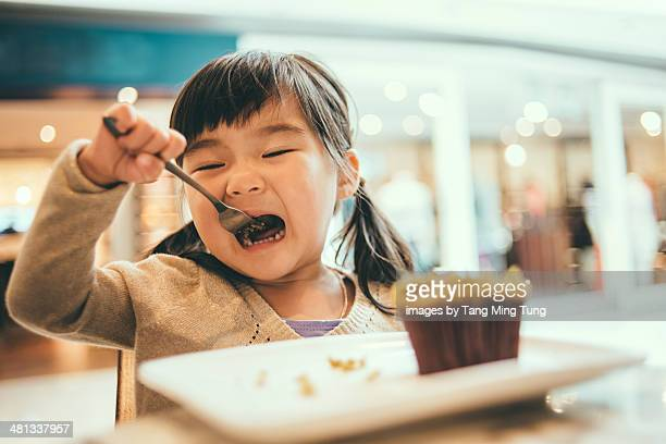 Toddler girl having muffin in a coffee shop