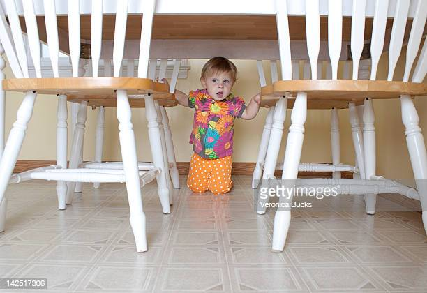 Toddler girl hiding under kitchen table