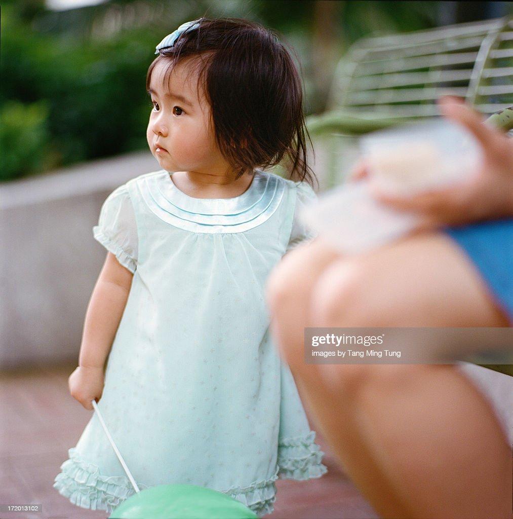 Toddler girl holding a green ballon standing : Stock Photo