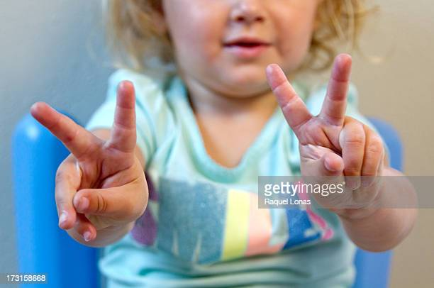 Toddler girl holding up two fingers on each hand